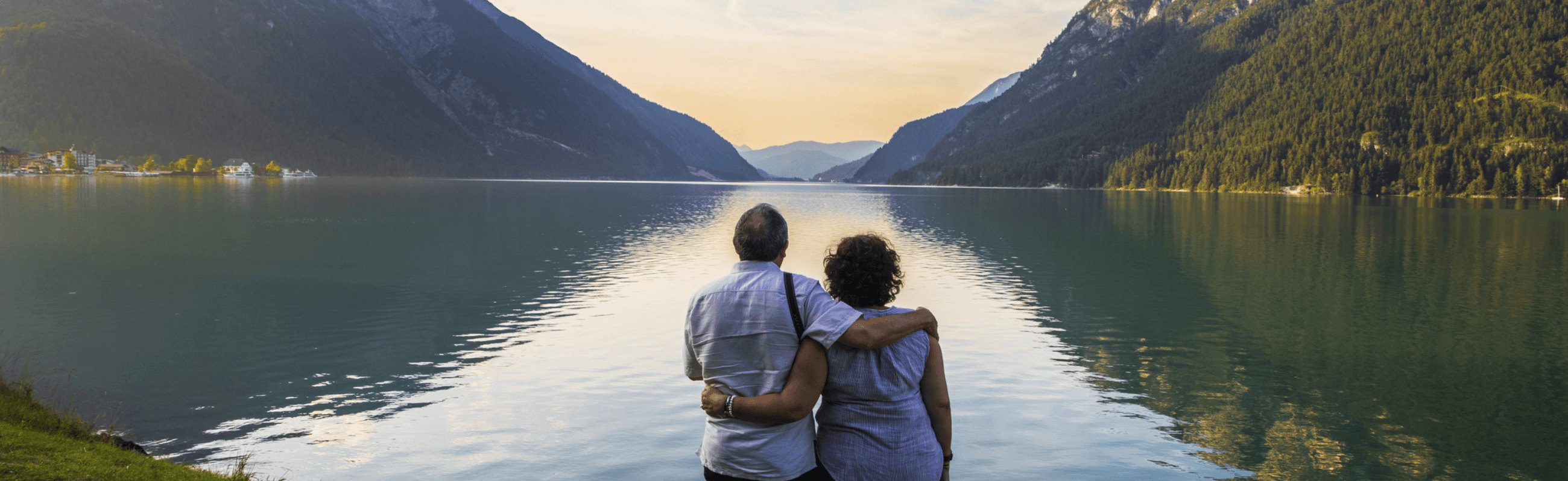Photograph of a couple enjoying a sunset over a lake